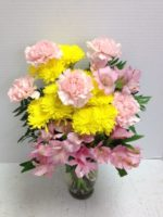 yellow and pink carnations in clear vase